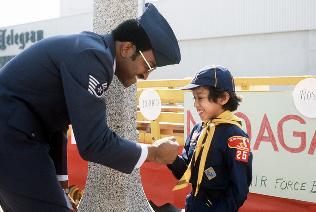 MASTER Sgt. Gary Kelly, a member of the Non-Commissioned Officers Academy Graduates Association (NCOAGA), meets cub scout Freddie Rodriguez. Base personnel helped handicapped scouts participate in the annual National Orange Show Parade