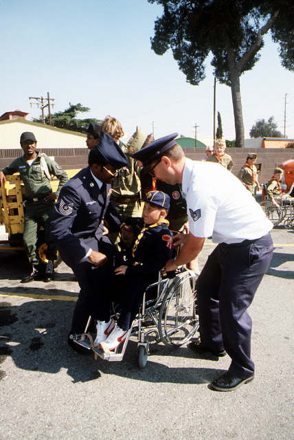 MASTER Sgt. Gary Kelly, a member of the Non-Commissioned Officers Academy Graduates Association (NCOAGA), and Technical Sgt. Ron David, cub master, help cub scout George Bunker into his wheel chair. Base personnel helped handicapped scouts participate in the annual National Orange Show Parade