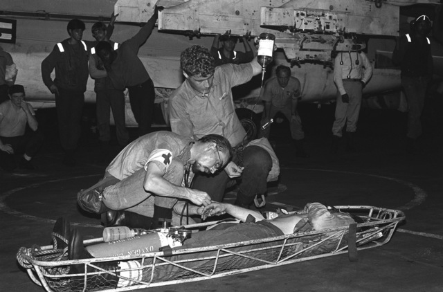 A hospital corpsmen inserts an intravenous (IV) needle into the hand of a smoke-inhalation victim following a fire in a berthing compartment aboard the aircraft carrier USS INDEPENDENCE (CV-62)