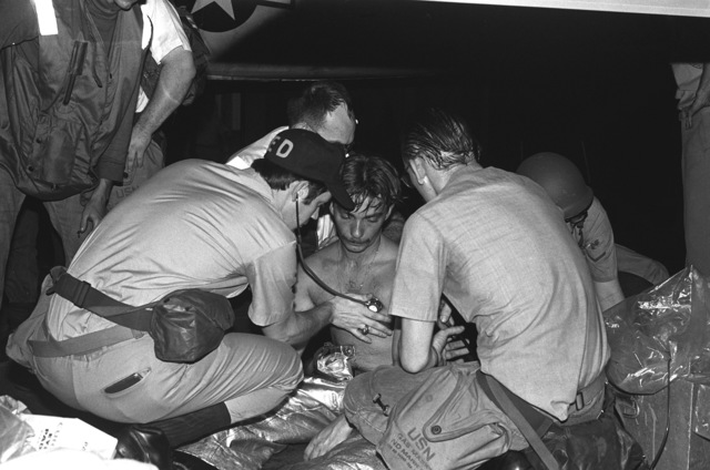 Hospital corpsmen take the blood pressure of a smoke-inhalation victim following a fire in a berthing compartment aboard the aircraft carrier USS INDEPENDENCE (CV-62)