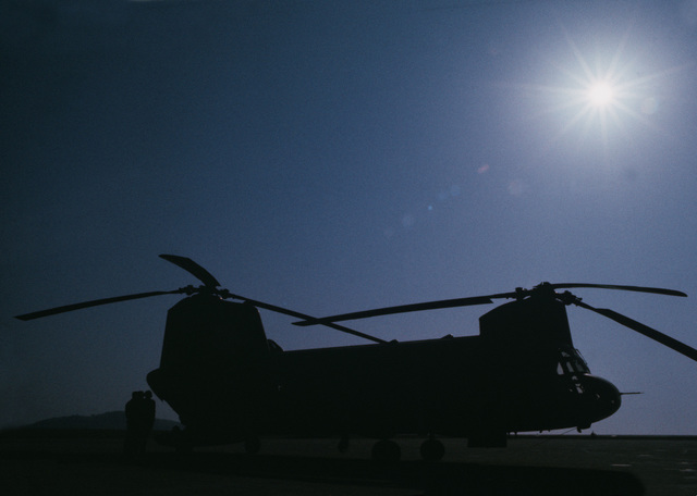 A US Army CH-47 Chinook helicopter is silhouetted against the sun during exercise TEAM SPIRIT '77