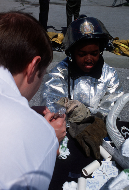An airman has a blood sample extracted from his wrist during a fire training exercise at Golden Mall