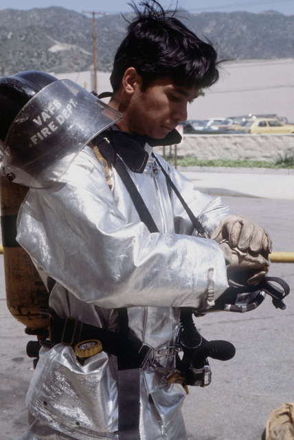 An airman wearing a fire protection suit prepares to participate in a fire training exercise at the Lockheed site