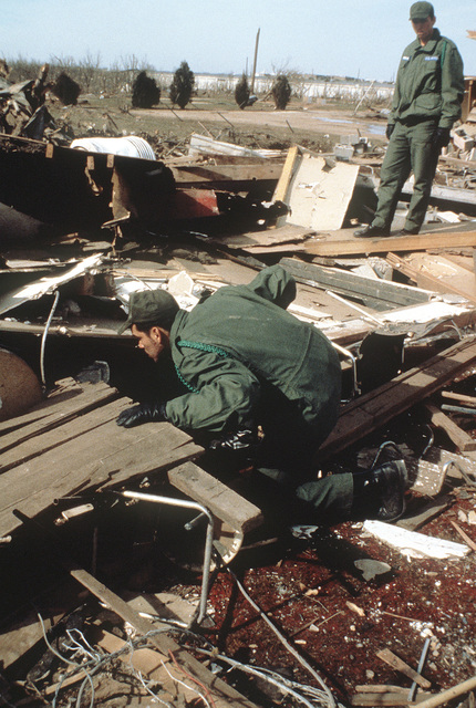 AIRMAN Salgado Fernandez, a pharmacy medical student at the Air Force Medical School at Sheppart Air Force Base, searches for survivors in the rubble of a bvuilding destroyed by a tornado