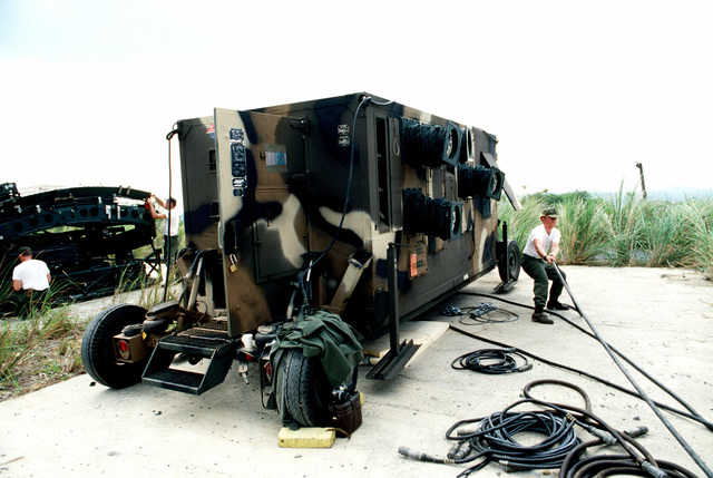 An airman connects power cables to an AN/TPS-43E radar van atop Cerro Gordo during US Southern Command canal defense Black Fury II. Units of the Army, Navy and air Force are taking part in the exercise