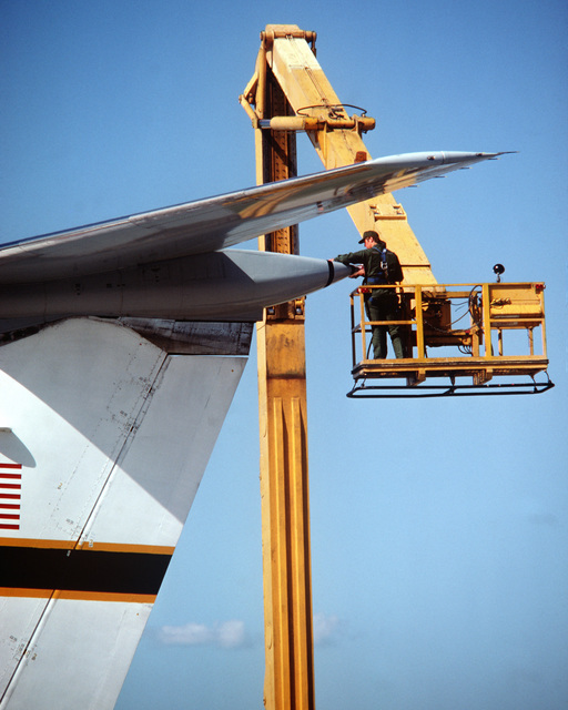 A ground crewman changes the warning light on the vertical stablizer of a Military Airlift Command C-141 Starlifter aircraft
