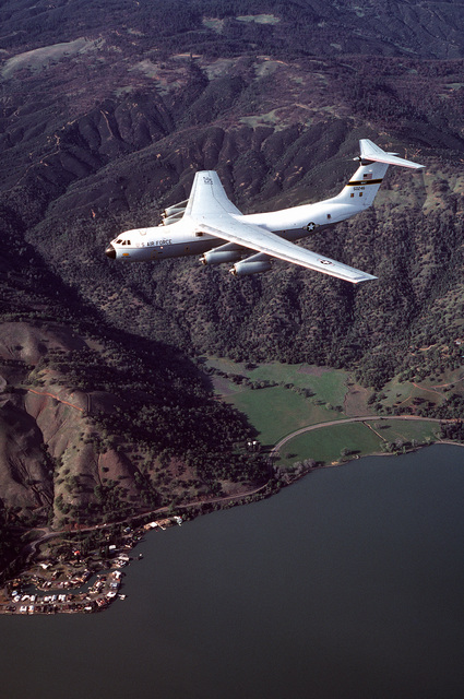 An air-to-air left side view of a C-141 Starlifter aircraft from the 710th Military Airlift Squadron, Air Force Reserve over Clear Lake
