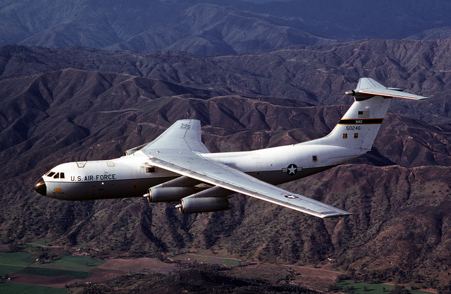 An air-to-air left side view of a C-141 Starlifter aircraft from the 710th Military Airlift Squadron, Air Force Reserve