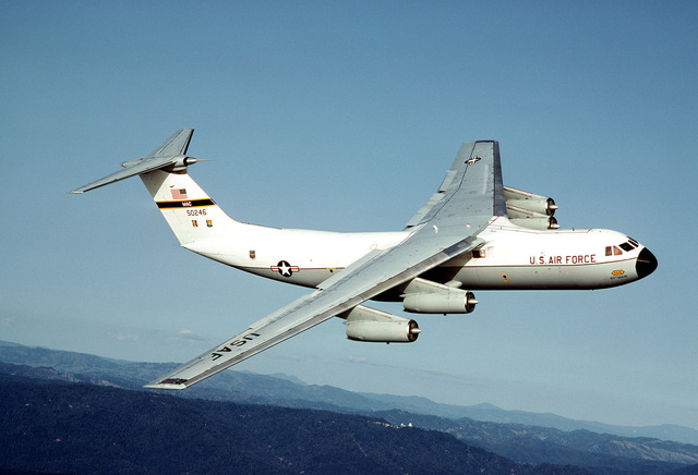 An air-to-air right side view of a C-141 Starlifter aircraft from the 710th Military Airlift Squadron, Air Force Reserve, over the coast near Ukiah