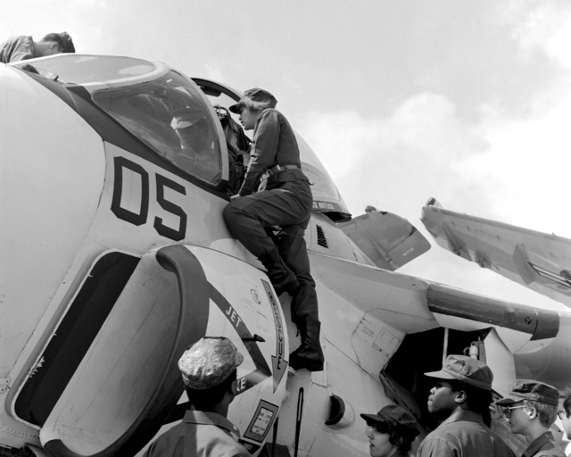 Junior ROTC student, SSGT Dawn Phillips stands on the side of an A-6E Intruder aircraft and looks into the cockpit