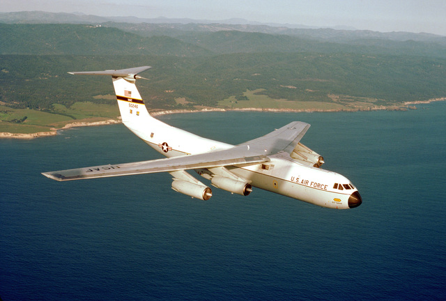 Northern California. An air-to-air right front view of a C-141 Starlifter aircraft from the 710th Military Airlift Squadron, Air Force Reserve, over the coast near Ukiah
