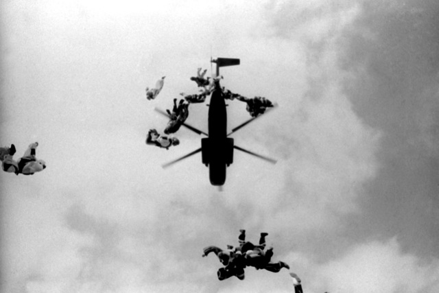 Eighteen Marines take a big first step from a CH-53 Sea Stallion helicopter. They are setting a record for a skydiving team. The previous all Marine record consisted of ten men skydiving together. This club was formed in March 1975 at Quantico
