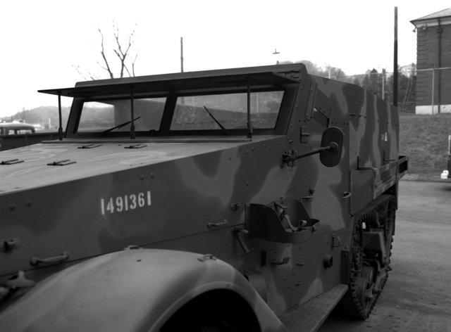 A Marine Corps personnel carrier, half track (M3), viewed from the left front with camouflage paint and without the canvas top