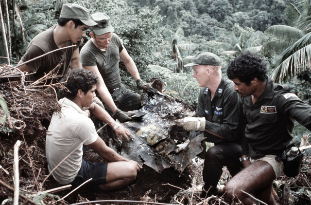 An expedition team from Howard Air Force Base, Canal Zone, examines a piece of wreckage from a World War II B-24D Liberator aircraft