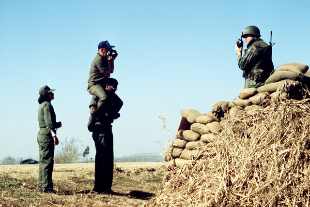 "TSGT Curtis Eddings sits on the shoulders of TSGT Michael Daniels to photograph a soldier, who is patrolling the area of the recent assassination of the South Korean president. The photo journalists are assigned to Detachment 6, 1363rd Audiovisual Squadron. Bi-monthly Aerospace Audio Visual Service PHOTO Contest, Color Entry, Jul. 1980, ""Team Work"""