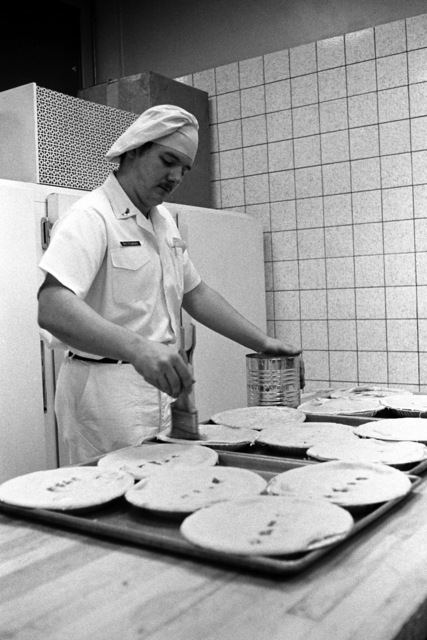 An airman puts toppings on pies in the Eifel dining facility