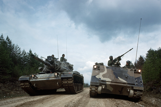 An M113 armored personnel carrier and an M60 main battle tank on maneuvers during a field training exercise