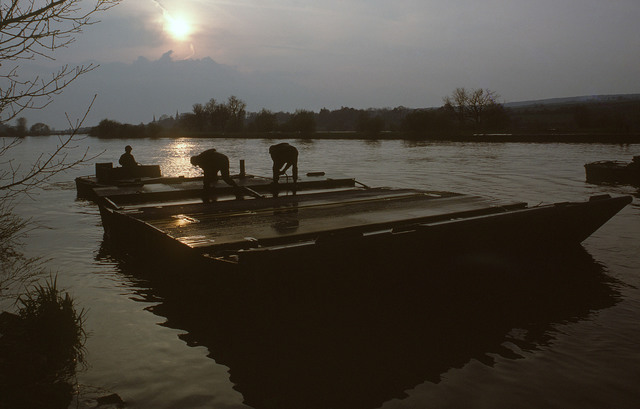 US Army soldiers maneuver a segment of floating bridge