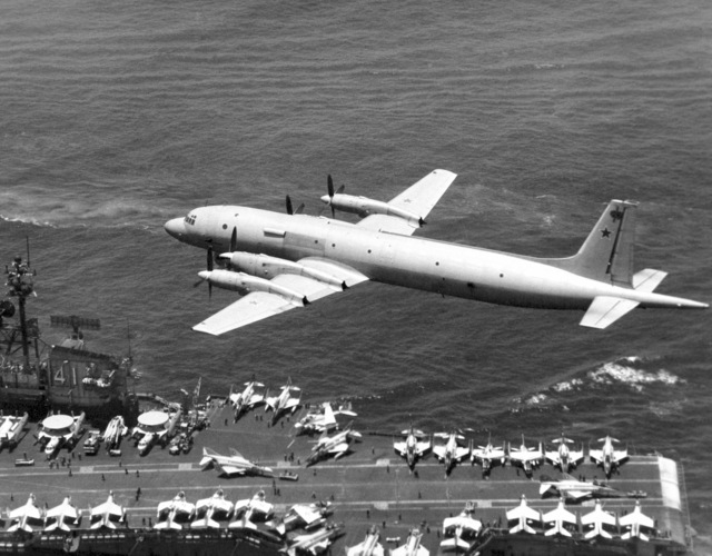 An air-to-air left rear view of a Soviet I1-38 May reconnaissance and anti-submarine warfare aircraft passing low over the flight deck of the aircraft carrier USS MIDWAY (CV 41)