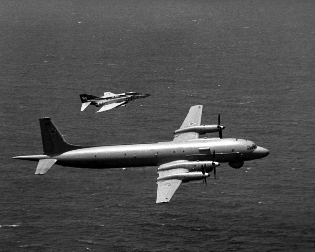 An air-to-air right side view of an F-4J Phantom II aircraft from Fighter Squadron 161 (VF-161) escorting a Soviet I1-38 May reconnaissance and anti-submarine aircraft. The Phantom is assigned aboard the aircraft carrier USS MIDWAY (CV-41)