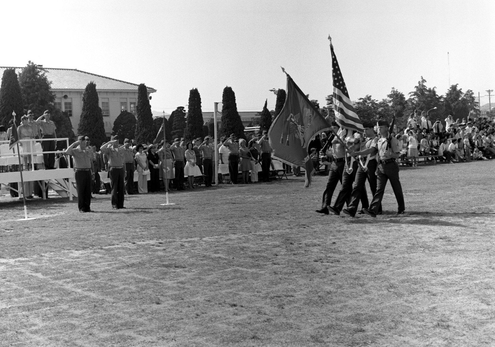 A Marine color guard passes in review during change of command ceremonies for COL Ralph D. Miller who is relieved by COL Speed F. Shea as commanding officer of the Marine Corps Air Station. COL Shea is on the far left side of the photograph