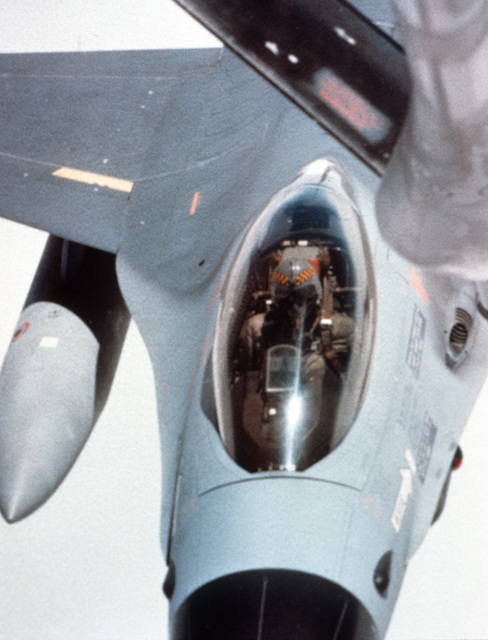 An air-to-air close-up view from the boom operator's window of an F-16 Fighting Falcon aircraft refueling
