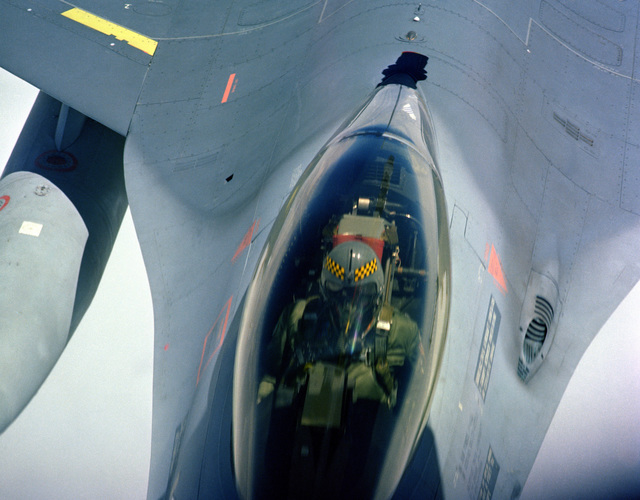 An air-to-air close-up view of the pilot of an F-16 Fighting Falcon aircraft looking up at a tanker aircraft during refueling as seen from the tanker's boom operator position