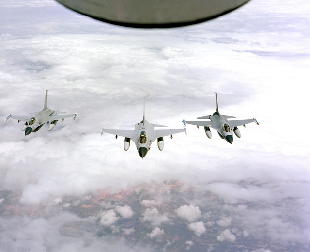 An air-to-air front view of three F-16 Fighting Falcon aircraft as they approach to refuel from a tanker aircraft