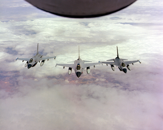 An air-to-air front view of three F-16 Fighting Falcon aircraft flying in close formation