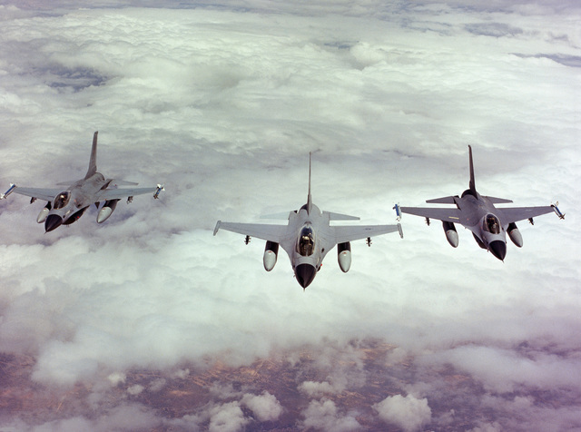An air-to-air front view of three F-16 Fighting Falcon aircraft in close formation