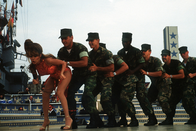 During the Bob Hope show aboard the amphibious assault ship USS IWO JIMA (LPH-2), singer and actress Charo leads a group of Marines around a stage