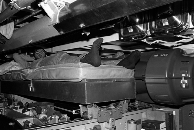 A crewman aboard the attack submarine USS Bonefish (SS-582) relaxes in his bunk during exercise Unitas XX