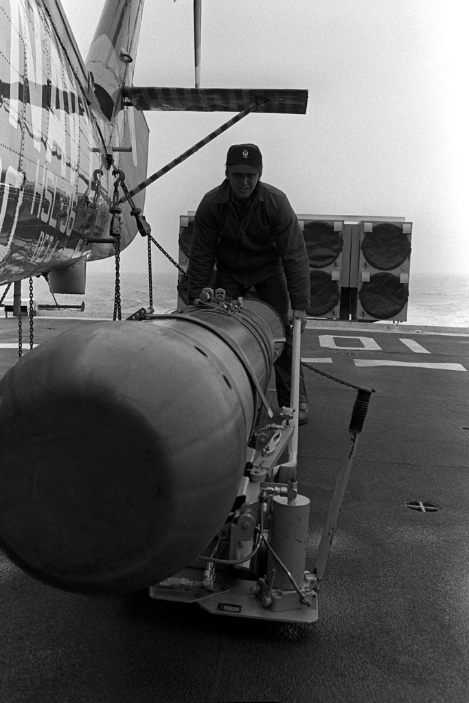 A crewman aboard the frigate USS TRIPPE (FF-1075) loads a Mark 46 anti-submarine warfare torpedo onto an SH-2F Seasprite light airborne multi-purpose system (LAMPS) helicopter, on the flight deck during exercise Unitas XX. The helicopter is assigned to Light Helicopter Anti-submarine Squadron 36 (HSL-36)