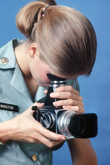 A female U.S. Army photographer demonstrates the use of a 70mm camera