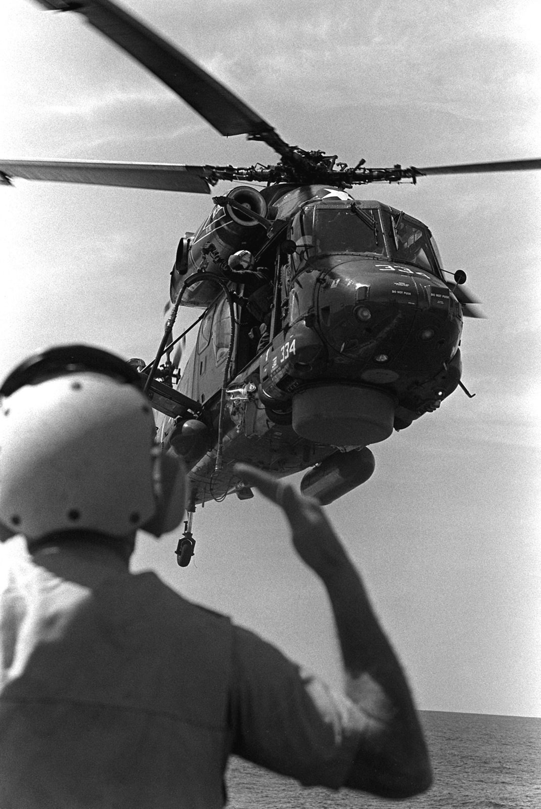 A Light Helicopter Anti-submarine Squadron 36 (HSL-36) SH-2F Seasprite light airborne multi-purpose system (LAMPS) helicopter is refueled in flight as a crewman guides it from the flight deck of the guided missile destroyer USS DEWEY (DDG-45), during exercise Unitas XX