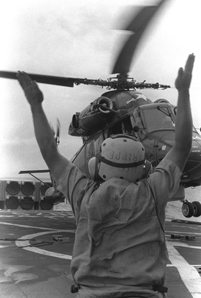 A Light Helicopter Anti-submarine Squadron 36 (HSL-36) SH-2F Seasprite light airborne multi-purpose system (LAMPS) helicopter on the flight deck of the frigate USS TRIPPE (FF-1075) as a crewman signals it for takeoff during exercise Unitas XX