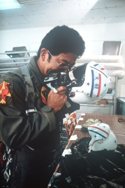 A member of the Hawaii Air National Guard checks his life support equipment before a flight