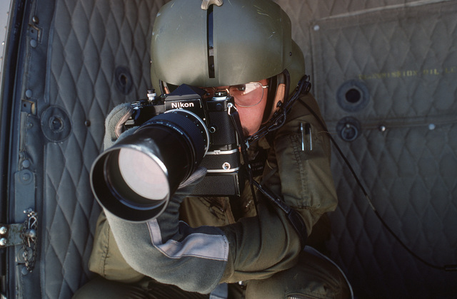 A US Army photographer demonstrates the use of a 35 mm single lens reflex camera with a telephoto lens for aerial photography