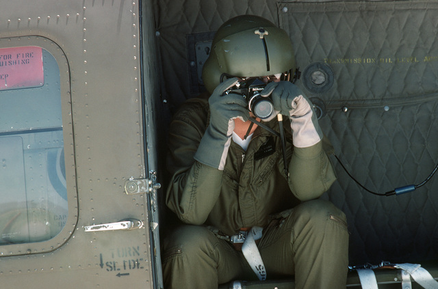 A US Army photographer demonstrates the use of a 35 mm single lens reflex camera for aerial photography