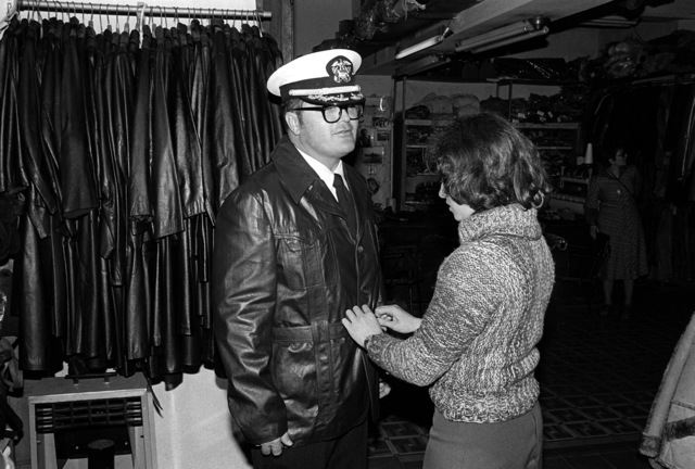 A U.S. Navy officer gets fitted for a leather jacket while on liberty during exercise Unitas XX