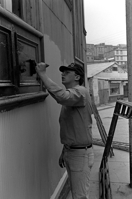 A U.S. sailor paints the outside of a building as part of a community relations program during exercise Unitas XX