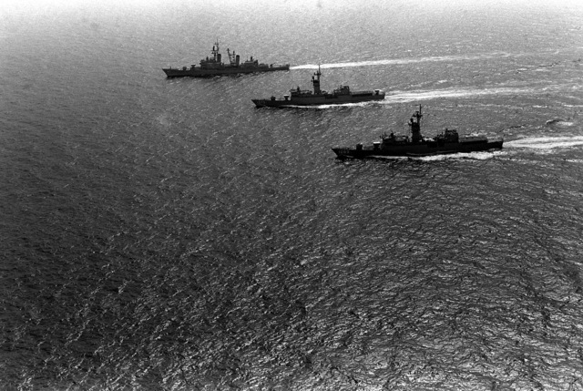 An aerial port beam view of exercise Unitas XX task force underway. From left to right are the guided missile destroyer USS DEWEY (DDG-45), the frigates USS TRIPPE (FF-1075) and USS JESSE L. BROWN (FF-1089)