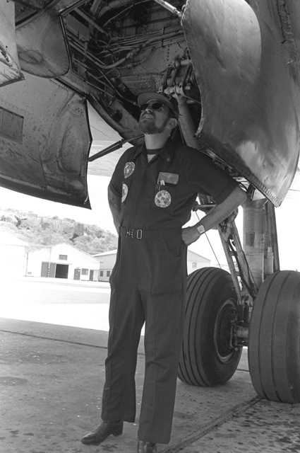 As the Navy show band prepares to leave, a crewman checks the landing gear during the preflight inspection of the aircraft