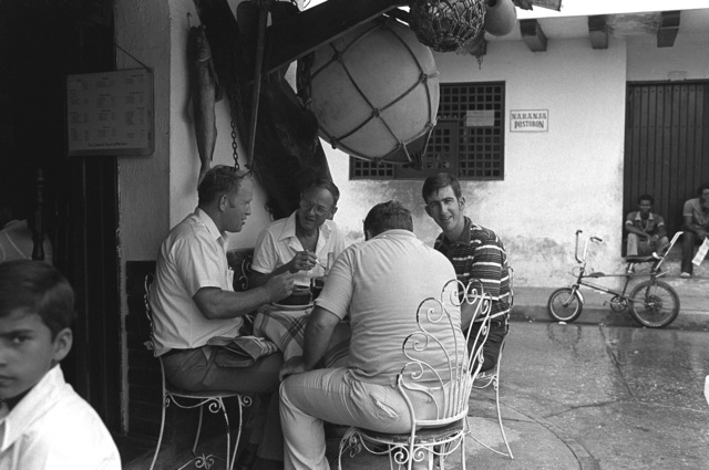 Crewmen from exercise Unitas XX sit at an outdoor cafe while on liberty