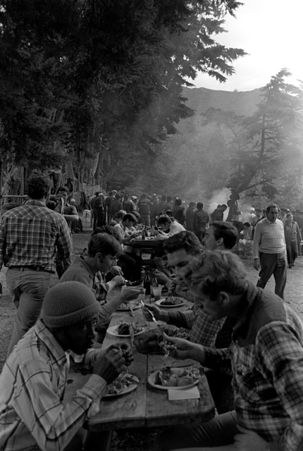 Crewmen from the Unitas XX task force sit at picnic tables and eat their meals at a party held during the exercise