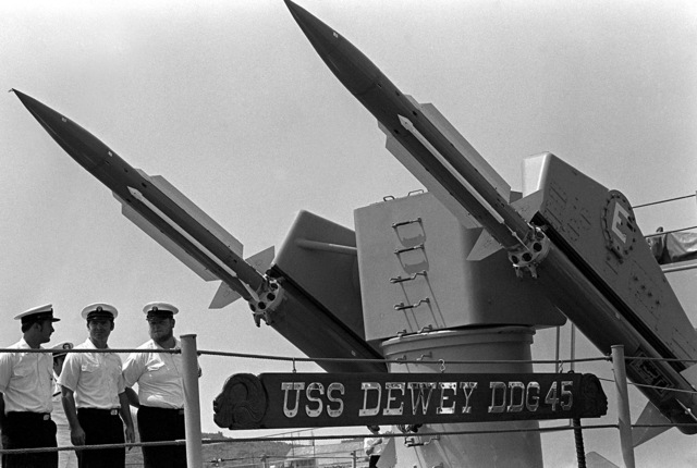 Crewmen stand at parade rest under the Mark 10 missile launcher aboard the guided missile destroyer USS DEWEY (DDG-45) as the ship gets underway for participation in exercise Unitas XX