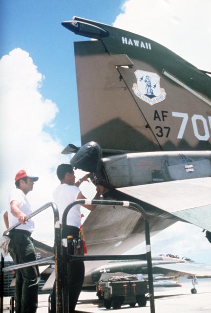 Ground crewman pack a drogue chute into the tail of a Hawaii Air National guard F-4C Phantom II aircraft