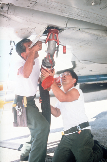 Members of the Hawaii Air National Guard attach a fuel hose to an aircraft