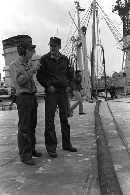 Two crewmen stand on the pier as one uses a radio head-set for communication purposes during exercise Unitas XX
