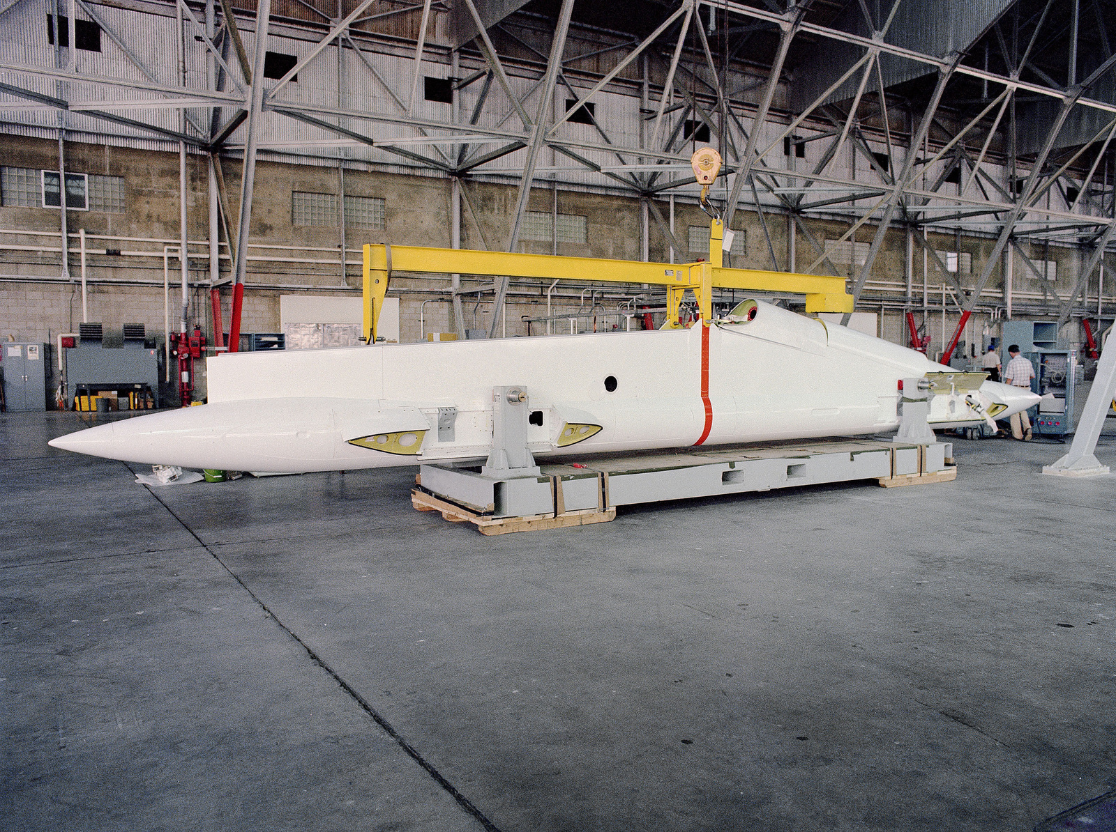 Side view of a B-52 Stratofortress aircraft wing pylon in a hangar